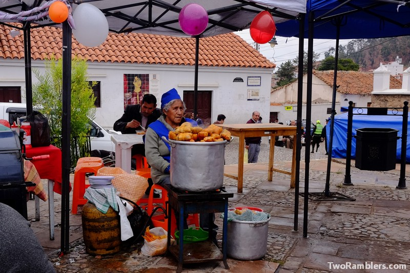 Lady with a big pot of humitas in front of her at a food stand