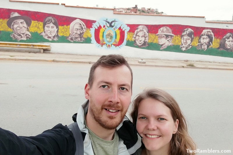 Two people in front of mural in colours of Bolivian flag