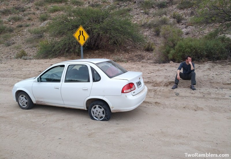 Car with flat tire on sand road